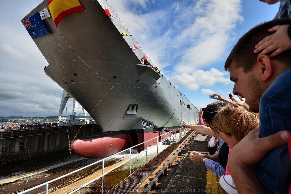 La peculiar silueta del «Adelaide» coronada por las banderas de España y Australia en su proa (Foto: Xoán Porto / Revista Naval)