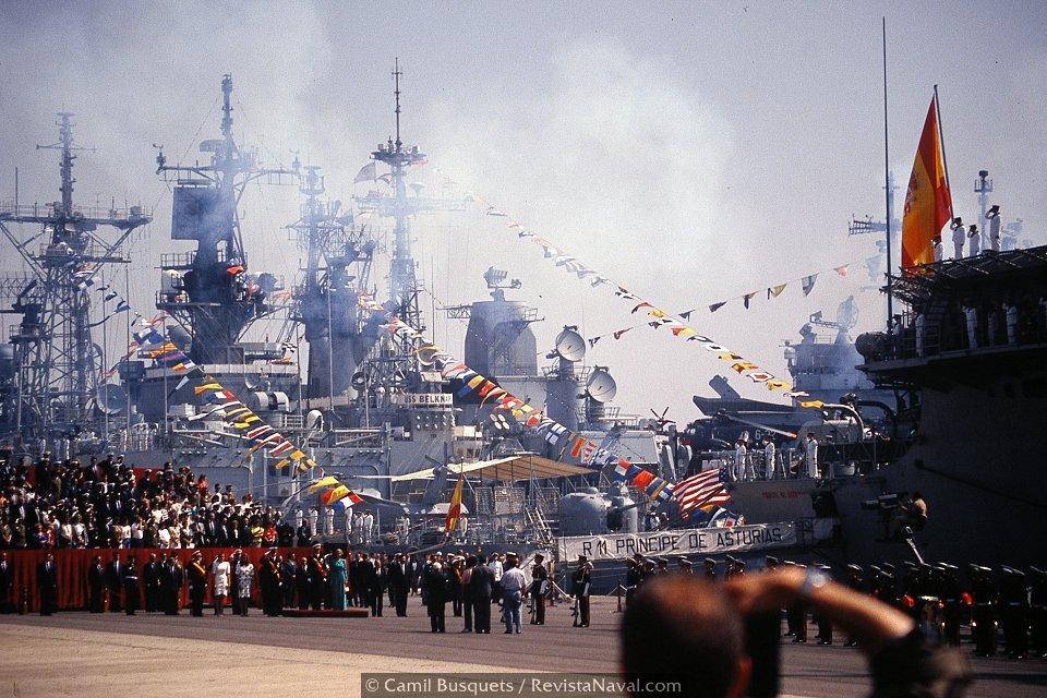 Vista general del escenario de la ceremonia, la tribuna de invitados y los buques atracados en el puerto, entre el humo de las salvas de ordenanza (Foto: Camil Busquets / Revista Naval)