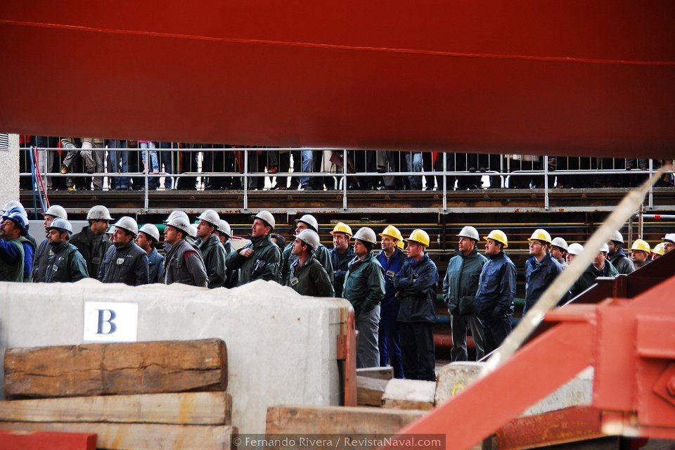 Bajo la quilla, los trabajadores del astillero y empresas auxiliares contemplan el desarrollo de los actos protocolarios en la tribuna de autoridades (Foto: Fernando Rivera/Revista Naval)